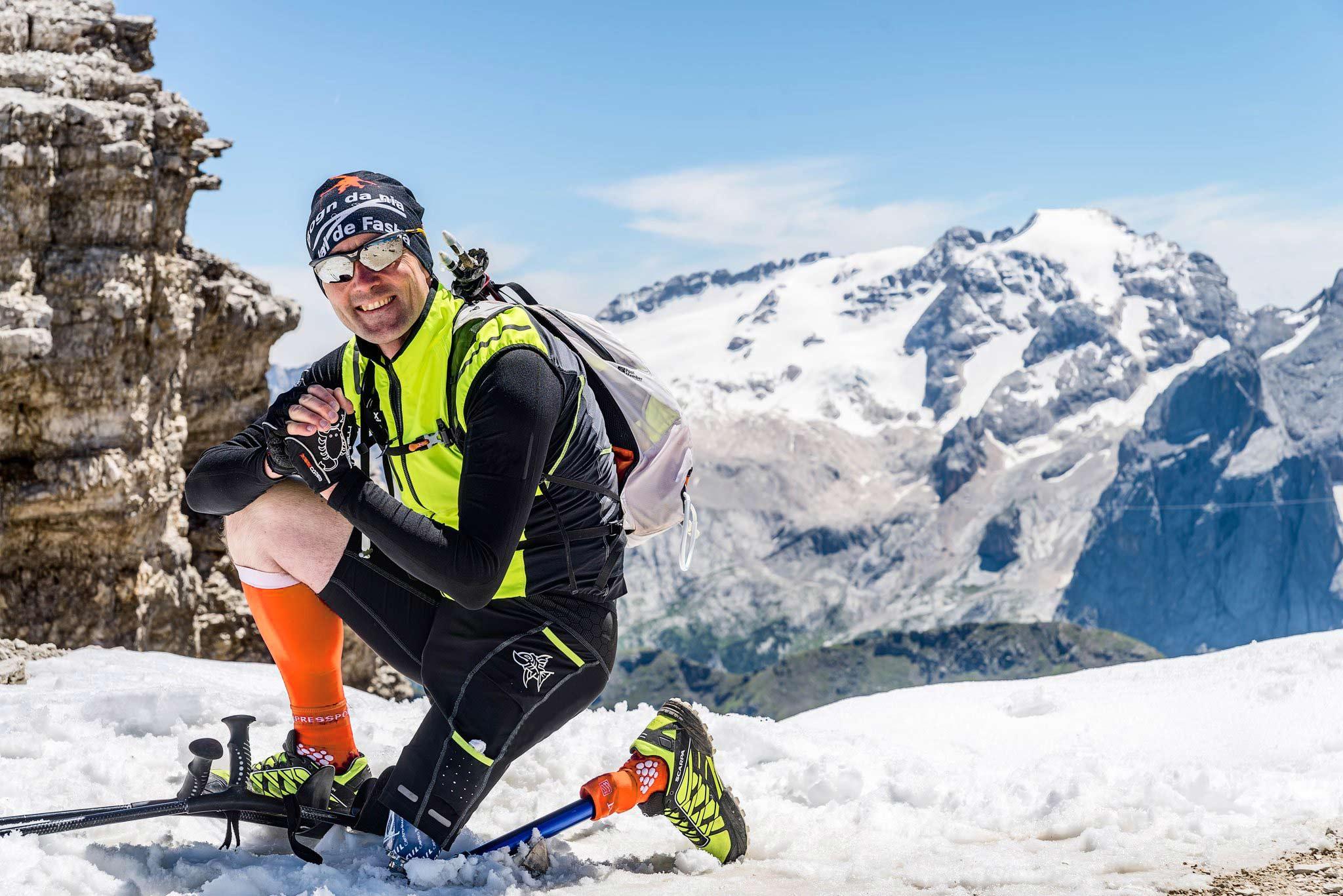Moreno Pesce in ginocchio tra la neve con paesaggio dolomitico nello sfondo